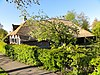 foto van Boerderij met staldeel met houten wanden onder oplopend rieten schilddak dat aansluit op rieten schilddak van woondeel