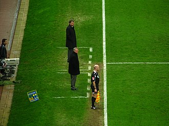 Technical area - White lines define the limits of each team's technical area at Manchester United's Old Trafford in 2009. The fourth official stands nearby.