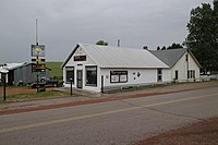 Old building with welcome sign and community bulletin board in Recluse, Wyoming.jpg