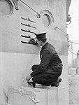 Ordinary Seaman P S Buckingham, keeping a record of U-boat kills on the side of the wheelhouse on board HMS HESPERUS, docked at Liverpool, 6 December 1943. A20897.jpg