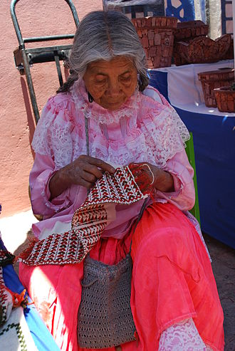 Tequisquiapan - Otomi woman embroidering at one of the crafts markets