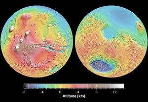 Geology of Mars - Mars Orbital Laser Altimeter (MOLA) colorized shaded-relief maps showing elevations in the western and eastern hemispheres of Mars. (Left): The western hemisphere is dominated by the Tharsis region (red and brown). Tall volcanoes appear white. Valles Marineris (blue) is the long gash-like feature to the right. (Right): Eastern hemisphere shows the cratered highlands (yellow to red) with the Hellas basin (deep blue/purple) at lower left. The Elysium province is at the upper right edge. Areas north of the dichotomy boundary appear as shades of blue on both maps.