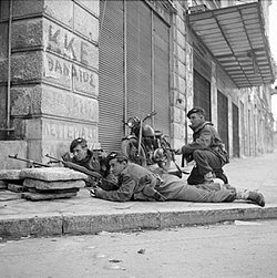 Paras from 5th (Scots) Parachute Battalion, 2nd Parachute Brigade, take cover on a street corner in Athens during operations against members of ELAS, 6 December 1944. NA20515.jpg