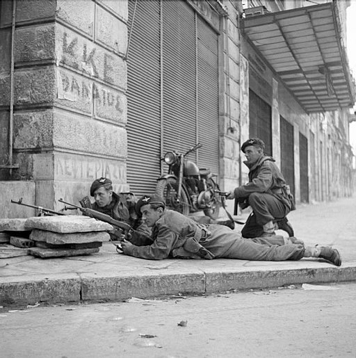 Paras from 5th (Scots) Parachute Battalion, 2nd Parachute Brigade, take cover on a street corner in Athens during operations against members of ELAS, 6 December 1944. NA20515