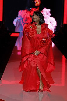 A woman in a red dress walks down a catwalk