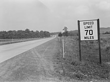 Black-and-white photo of highway with old 70-mph sign