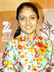 A smiling Rinku Rajguru, in a multi-coloured top