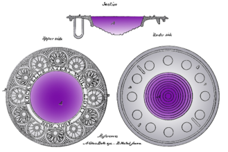 A large circular glass lens with a flat top and a stepped domed bottom. The glass is purple, with the shade darkening towards the top. The glass is set in a wide and ornate circular frame engraved with a semi-geometric ring-of-roundels design that looks a bit Art Deco, although from 1834.