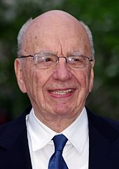 An old man with a bald head and a black suit, as well as glasses, is standing, smiling.