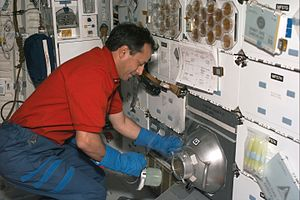 STS-93 - CNES astronaut Michel Tognini works with a nitrogen freezer, which supported the Plant Growth Investigations in Microgravity (PGIM) and Biological Research in Canisters (BRIC) experiments on this mission which took place in 1999