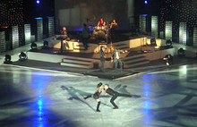 A male and female figure skater spin around each other on the ice while a band plays in the background.