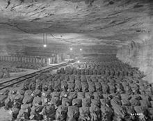 Row after row of sacks of gold, neatly stacked in a mine, with a mine rail running down the middle.
