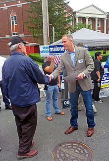 A man wearing a jacket, shirt, dark jeans and loafers, leaning forward and shaking hands with an older man wearing a black baseball hat and blue windbreaker.