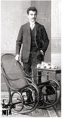 Man in suit standing next to rocking chair and table