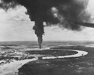 Aerial black and white photo of a river with buildings on its left-hand shore. A large column of smoke is rising from near the bank of the river.