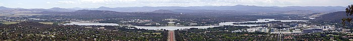 Panoramic view from a mountain overlooking the lake from north to south. View is Axially along Anzac Parade and Parliament House is directly opposite. A group of office blocks and small skyscrapers can be seen at right, the city centre.