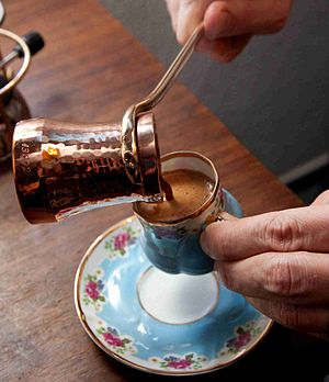 Turkish coffee - A cup of Turkish coffee, served from a copper cezve, in Turkey.