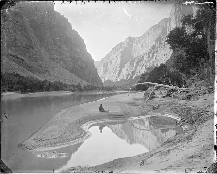File:The heart of Lodore, Green River-F.S. Dellenbaugh is seated and reflected in the water. Beaman photo 1871. Old No.... - NARA - 517793.jpg