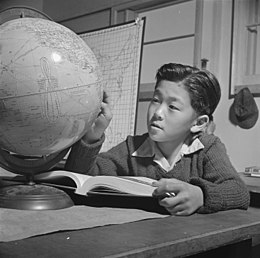 Topaz, Utah. A globe is used by this pupil in the high first grade, to assist in his geography lesson. - NARA - 536993.jpg