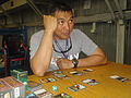 U.S. Army Chief Warrant Officer 2 Eduardo Macaraeg, a personnel technician, listens as his opponent during a game of Magic- The Gathering in the Moral Welfare and Recreation Hall at Camp Bondsteel, Pristina 110708-A-XV045-001.jpg