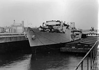 USS Agawam (AOG-6) at Mississippi i River Lock No. 15, in tow of the Federal Barge Line's Towboat Huck Finn, 12 November 1943..jpg