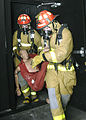 US Navy 040427-N-4469F-002 Damage Controlman 3rd Class Jason Lockenwitz of West Stockbridge, Mass. and Damage Controlman Fireman Carl Cross of Quarryville, Pa. simulate rescuing a victim during the Damage Control Olympics.jpg