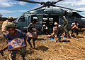 US Navy 050113-N-8629M-269 Victims of the Dec. 26 South East Asian Tsunami anxiously grab supplies delivered by an MH-60S Knighthawk from Helicopter Combat Support Squadron Five (HC-5).jpg