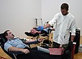 US Navy 060830-N-1755G-001 U.S. Army Spc. Brandon Branch, right, of Albuquerque, N.M. and the Armed Services Blood Bank Center at Fort Lewis, explains to Electrician's Mate 3rd Class Christopher Hinds, of Webb City, Mo., how he.jpg