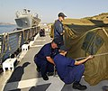 US Navy 080822-N-0780F-001 Crewmembers aboard the U.S. Coast Guard Cutter Dallas (WHEC 716) cover and secure a cargo of supplies.jpg