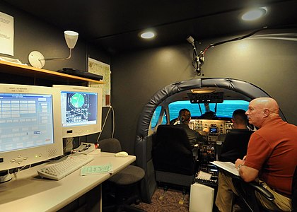US Navy 081008-N-2728S-071 Ensign Ruth Roberson and Air Force 2nd Lt. Denny Paulson take flight in the TC12B Visual Simulator during ground training exercises.jpg