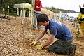 US Navy 081024-N-7952W-001 Daniel Barth from Sioux Falls, S.D., plants one of 1,400 small trees and shrubs along a stretch of the Potomac River that the Navy is working to stabilize at Naval Support Facility Indian Head, Md.jpg