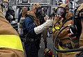 US Navy 090716-N-0807W-182 Sailors assigned to the mine warfare ship USS Avenger (MCM 1) damage control fire party check for a seal on the mask of their self contained breathing apparatus during a main space fire drill.jpg
