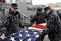 US Navy 100425-N-3542S-057 Sailors aboard the guided-missile destroyer USS Laboon (DDG 58) fold the American flag after shifting colors while departing Faslane, Scotland.jpg