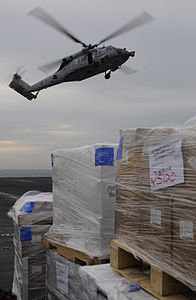 US Navy 120213-N-DH811-041 An MH-60S Sea Hawk helicopter assigned to the Golden Falcons of Helicopter Sea Combat Squadron (HSC) 12 drops off cargo.jpg