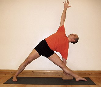 Iyengar Yoga - A student performing Uttitha Trikonasana, triangle pose, one of the basic standing poses in Iyengar Yoga