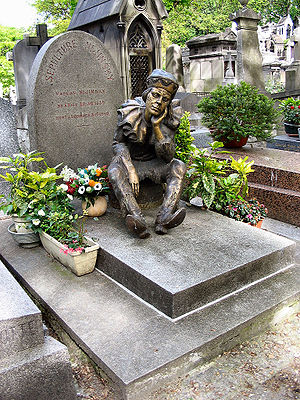 Petrushka - Tombstone of Vaslav Nijinsky in Montmartre Cemetery in Paris. The statue, donated by Serge Lifar, shows Nijinsky as the puppet Petrushka.