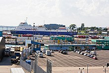 In this photograph, many large containers and other cargo are lined up in the city's ferry port. A ferry can be seen docked in the background.