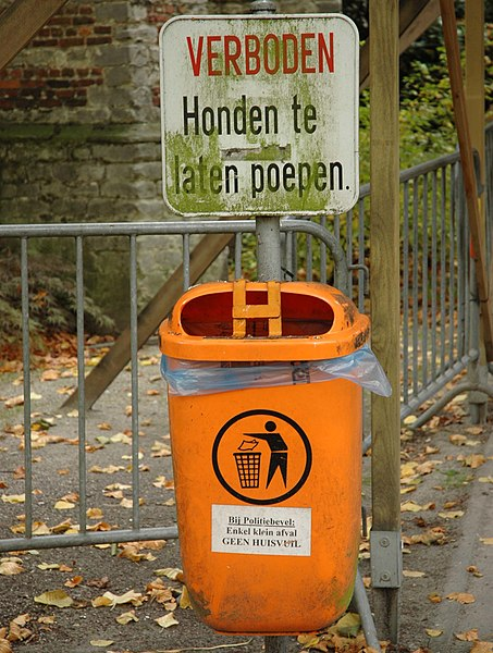 "Sign ""prohibited to let dogs defecate"" and a trash bin in Kontich, Belgium."