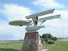 A roadside replica starship atop a stone base