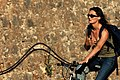 Woman in a Bicycle (8293372133).jpg