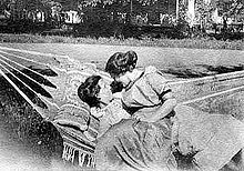 Black and white photo of two women sitting in a hammock in turn of the 20th century dresses; one reclines and the other sits on her lap and wraps her arm around the other, both staring at each other.