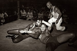 Professional wrestling - A professional wrestling match in 1938: two wrestlers grapple in a wrestling ring while a referee (in white on the right) looks on