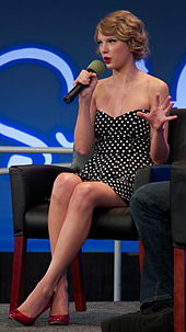 Taylor Swift speaks into a microphone, wearing a navy polka-dot dress and red heels