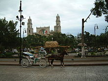 Scene of a plaza, with a horse and carriage in the foreground.