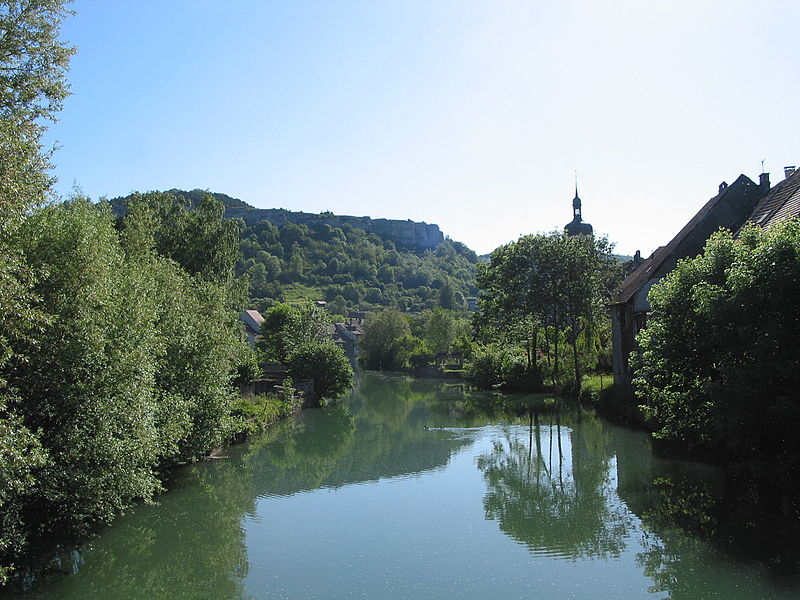 "Ornans (Doubs - France), the site of the ""Miroir d'Ornans"" with the clifs, the areas of the city along the Loue river and the church of Saint Lawrence."