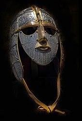 Photographie d'un casque métallique équipé de garde-joues, d'un masque facial et d'une jugulaire en cuir. La surface métallique est décorée avec des motifs finement ciselés, tandis que certains éléments sont dorés.