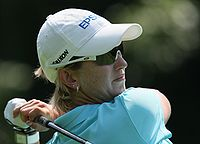 A blonde-haired woman in a white hat and light blue shirt holding a golf club at the end of a swing