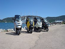 Four BMW C1 scooters parked side by side in front of a lake, with mountains and the masts of a large ship in the background