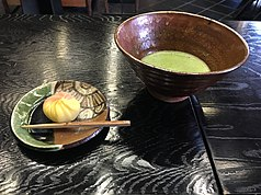 Bowl of macha green tea and small sweet on an oribe plate, at the Tōsui-an (陶翠庵) tea house at the Aichi Prefectural Ceramic Museum. The chawan is Ido type by Yamada Kazutoshi (山田和俊), the Oribe ware plate is from the ceramic craft studio of the museum done by staff.