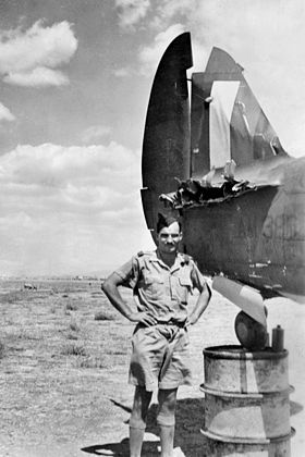 Man in khaki shirt and shorts, wearing forage cap, beside aircraft missing part of tailplane